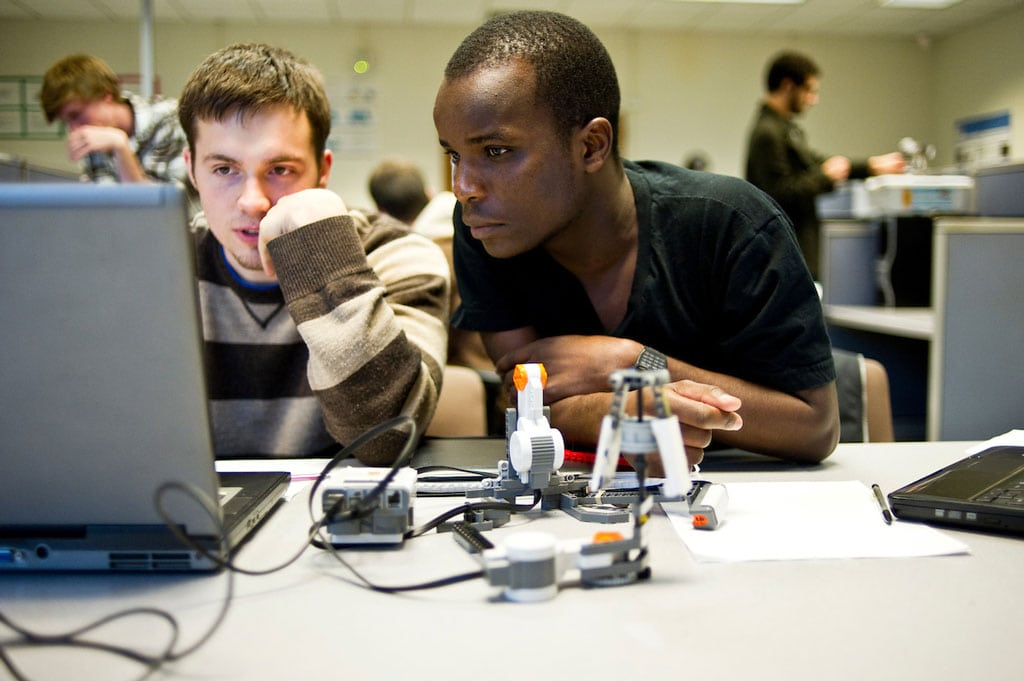 Two young men sit at a table reading a laptop screen together.
