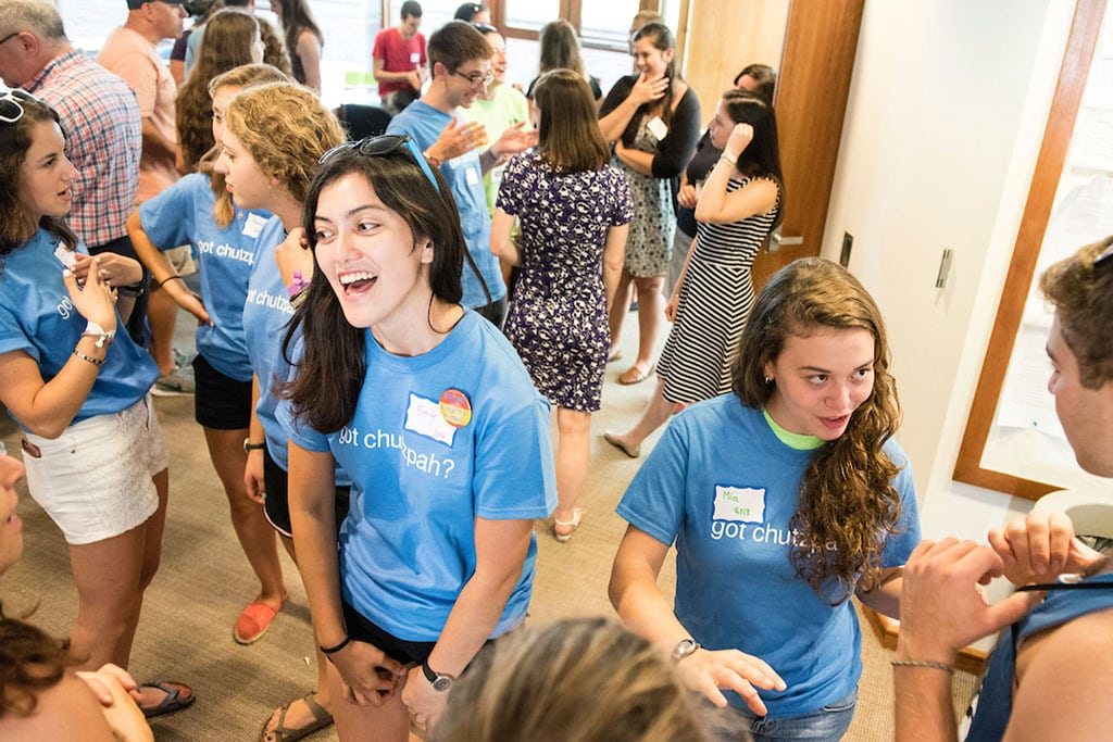Students wearing light blue t-shirts and name tags mingle with other students at a gathering.