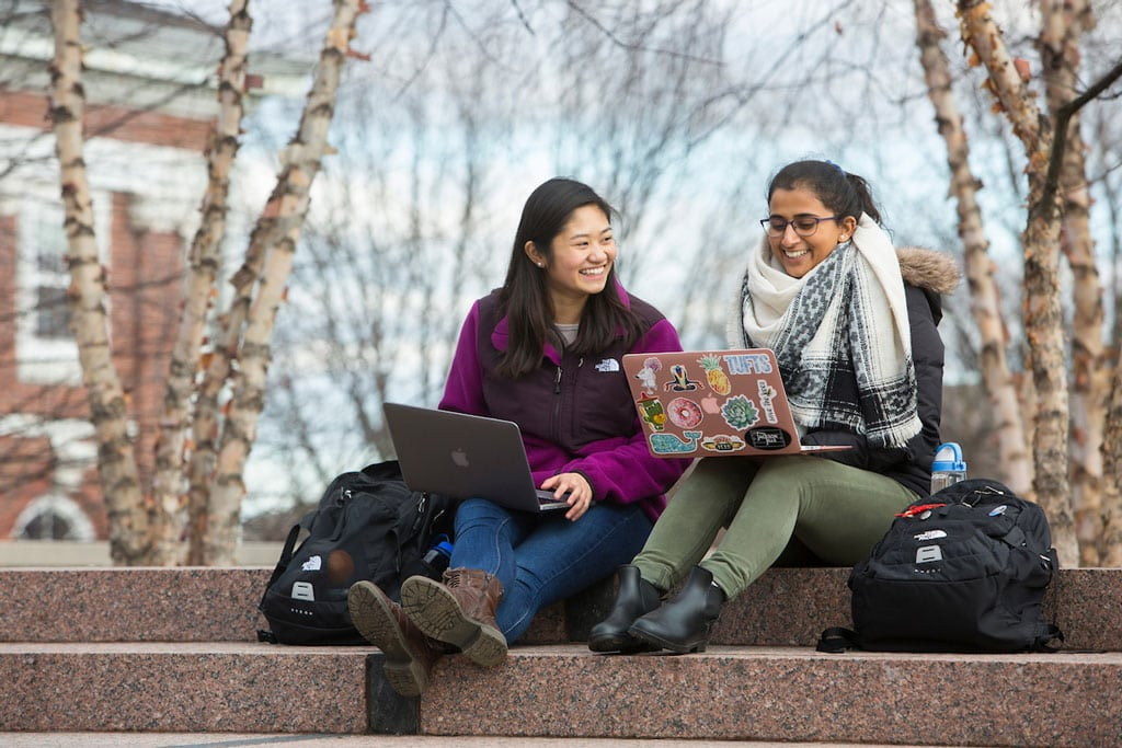 Two young women smile in acknowledgment of one another as they sit side by side on steps outside wearing jackets and using laptops.