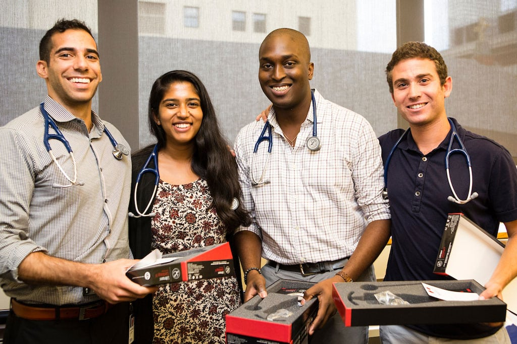 First-year medical students stand next to each other and smile as they receive their stethoscopes in the Sackler Center in 2017.