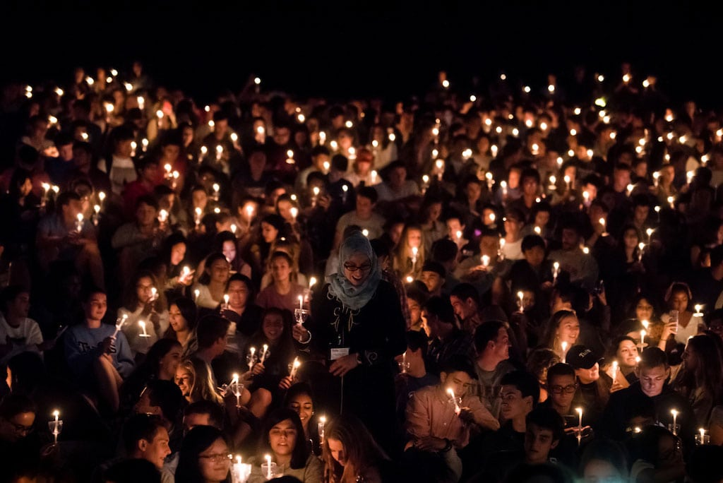 The Muslim chaplain makes her way through a sea of newly-minted Jumbos holding lit candles on the hill after passing the flame for the lighting ceremony on the evening of Matriculation in 2017.
