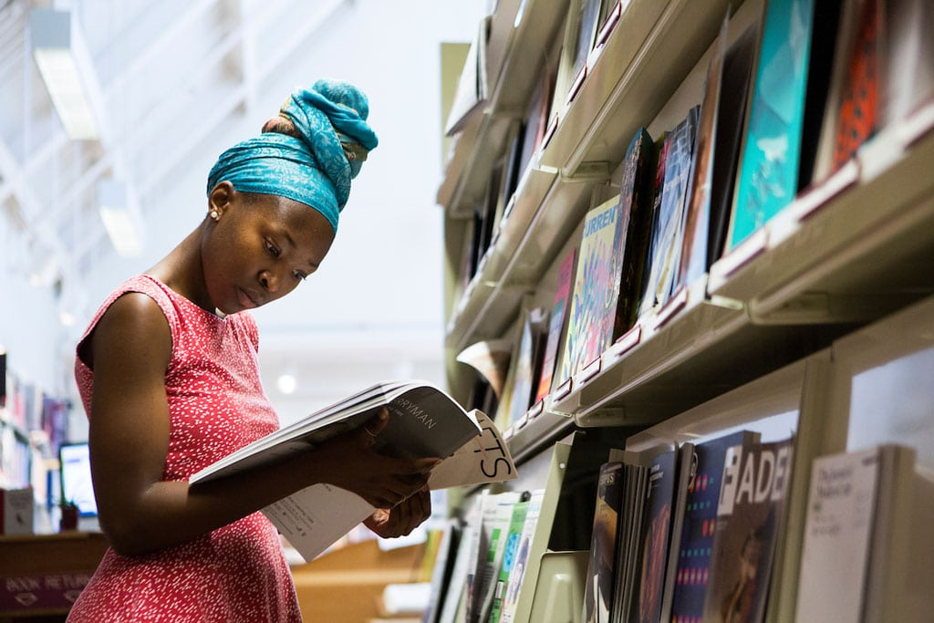 A woman wearing a dress in a red and white print and adorned in a blue head scarf reads a book while standing in front of a book shelf filled with other reading material.