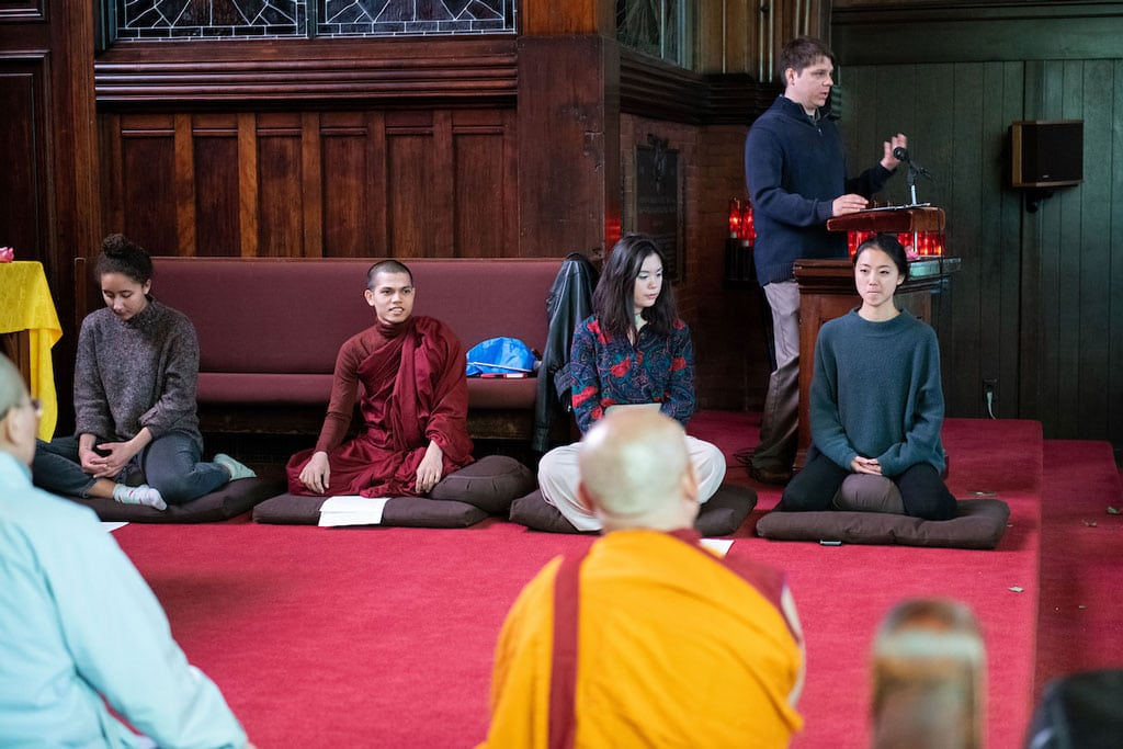 Young men and women sit on pillows as part of a Buddhist event.