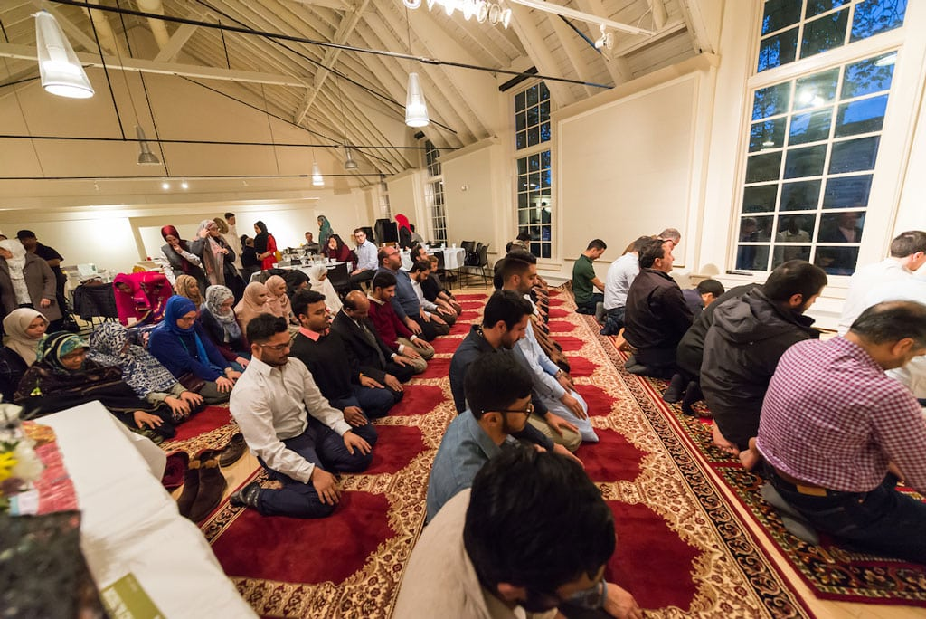 Muslim students pray together while kneeling on the floor in rows inside a large hall adorned with hanging lights.