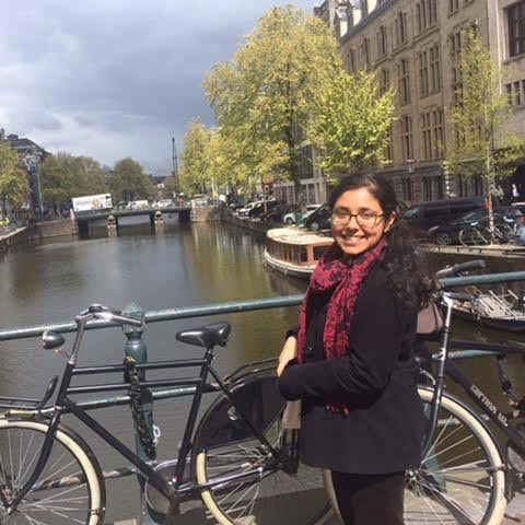 Student Palak Khanna, of A&S/Fletcher, poses outside next to bikes by a river.