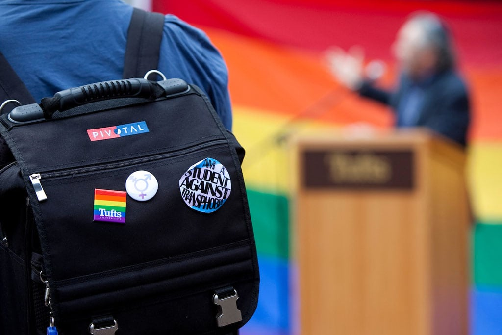An attendee wearing a backpack decorated with buttons supporting LGBTQ rights listens to Rabbi Jeffrey Summit speak at the Tufts Queer Straight Alliance's National Coming Out Day Rally in 2011.