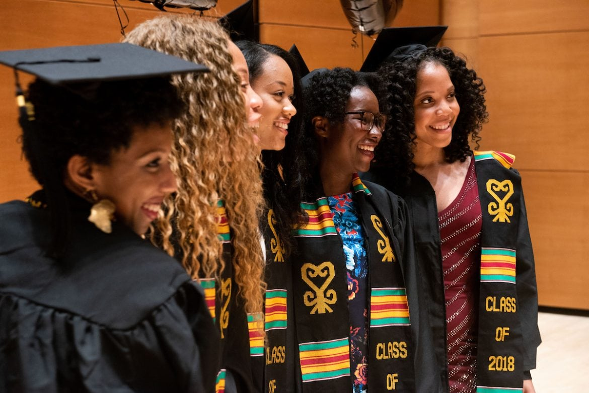 Group of women of color pose for a photo in graduation caps and gowns.