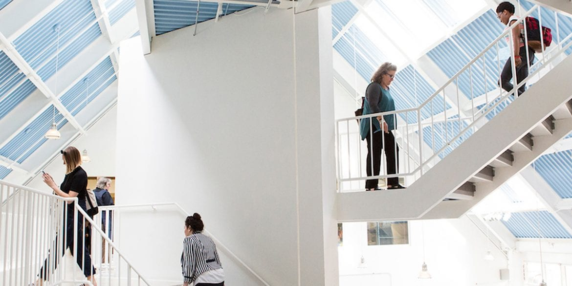 Students walk up and down white staircases in a hall with high ceilings.
